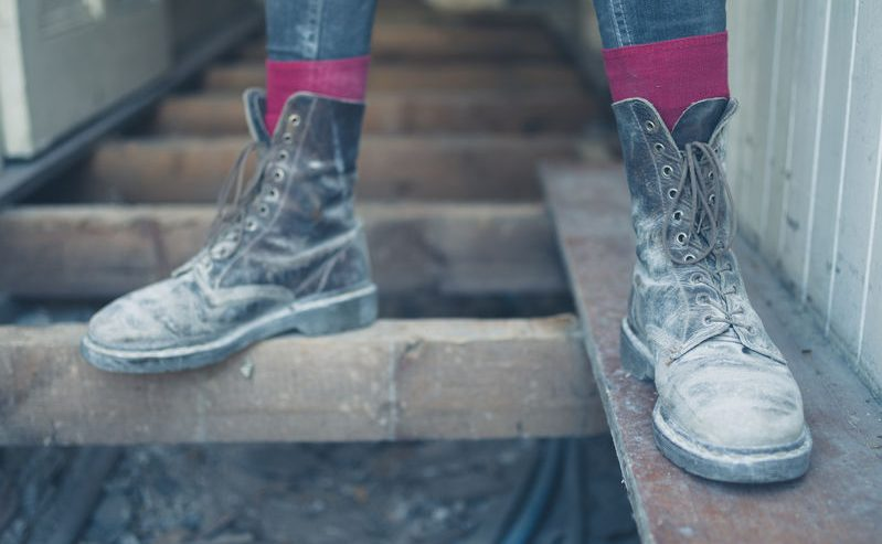 the feet of a worker wearing dirty old boots standing on the floor joists in a house undergoing renovations