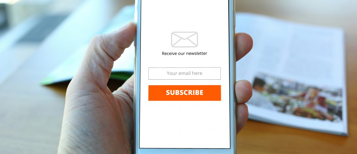 Hand holding smartphone with receive newsletter form on cafe background